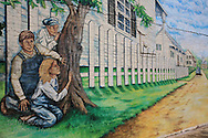 Outdoor mural in author Harper Lee's hometown depicts Scout, Jem and Dill hiding behind tree to spy on Boo Radley in scene from To Kill a Mockingbird; Monroeville, Alabama.