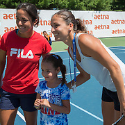 August 19, 2014, New Haven, CT:<br /> Arantxa Parra Santonja and Silvia Soler-Espinosa pose for a photograph with a girl during the Latino Day tennis clinic on day five of the 2014 Connecticut Open at the Yale University Tennis Center in New Haven, Connecticut Tuesday, August 19, 2014.<br /> (Photo by Billie Weiss/Connecticut Open)