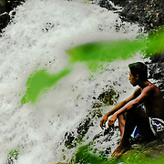 A young emberá Indian sits by the side of the Dozake Villakirua waterfalls in the Chagres River.  The Emberás are one of the seven indigenous groups still present in Panama.  They are usually find by the Chagres River in the Panama Canal protected areas as well as in the mountains and rivers of the Darien jungle