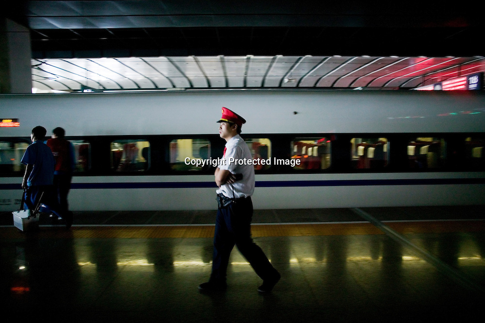 Beijing, September 11 , 2011 : a conductor walks past the TGV on the platform.the passenger-dedicated trunk line opened in June 2011, reducing the 1,318 km journey between Beijing and Shanghai to less than 5 hours. Trains reach top speeds of 300 km/h (186 mph) for the entire trip.