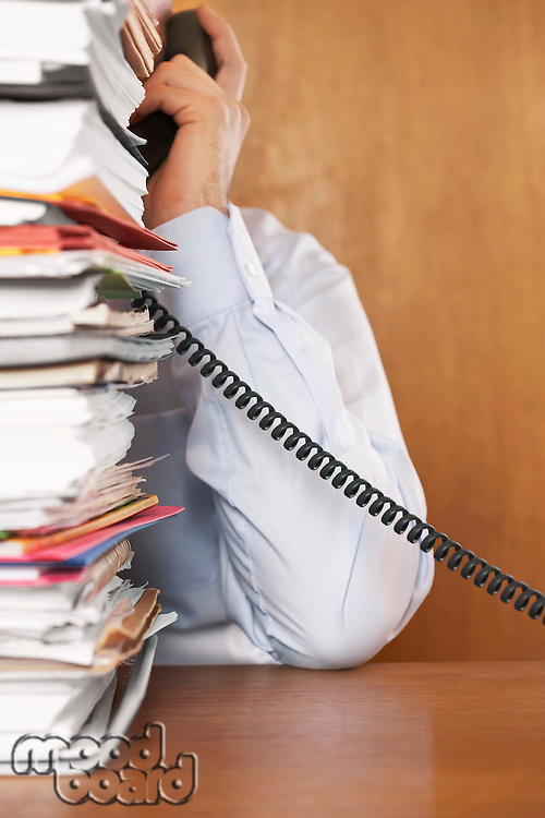 Man talking on telephone mid section behind stack of paperwork at desk