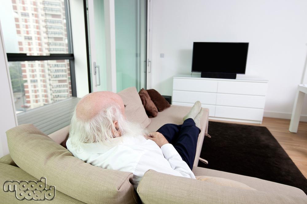 Senior man watching television in apartment