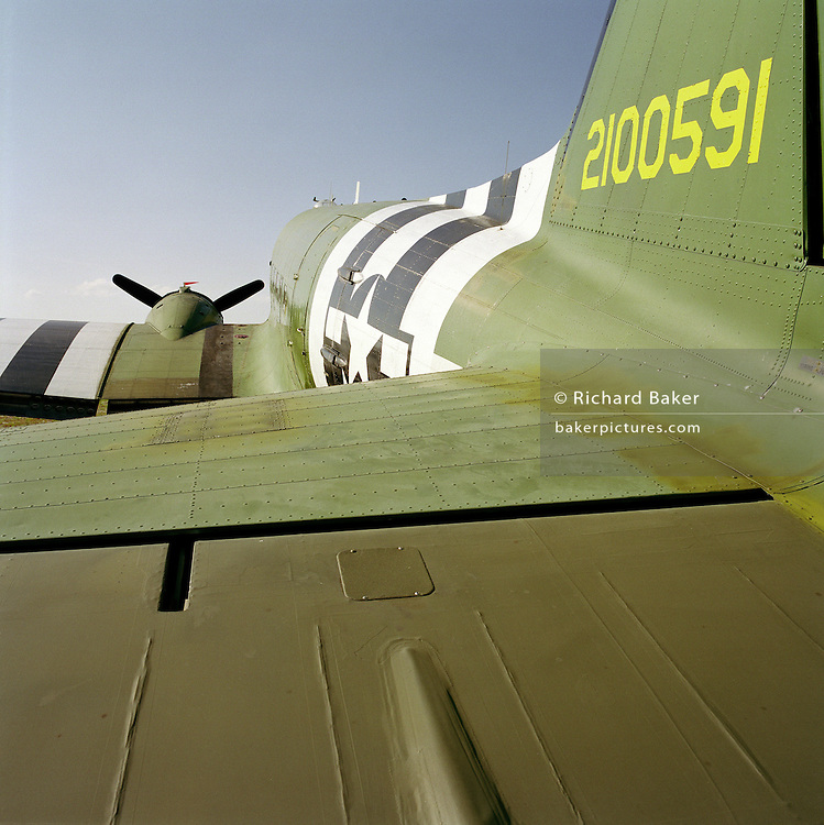 "A view along the fuselage of a DC3 Dakota, from its tail aileron to its propeller. Pointing upwards as it sits on a low tail wheel and with one of its 4 propellers still against a blue sky, we see the plane painted in the colours that many appeared in during the D-Day landings in June 1944, from where paratroopers jumped out for the eventual invasion of German-occupied France. The Douglas DC-3 is a fixed-wing propeller-driven airliner. Its speed and range revolutionized air transport in the 1930s and 1940s. Its lasting impact on the airline industry and World War II makes it one of the most significant transport aircraft ever made. Many DC-3s and converted C-47s are still used in all parts of the world. The designation ""DC"" stands for ""Douglas Commercial""."