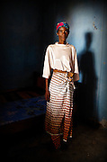 A Ghanaian woman stands inside her home - a dark, empty room - where she lived through the final stages of AIDS alone and in silence. <br />