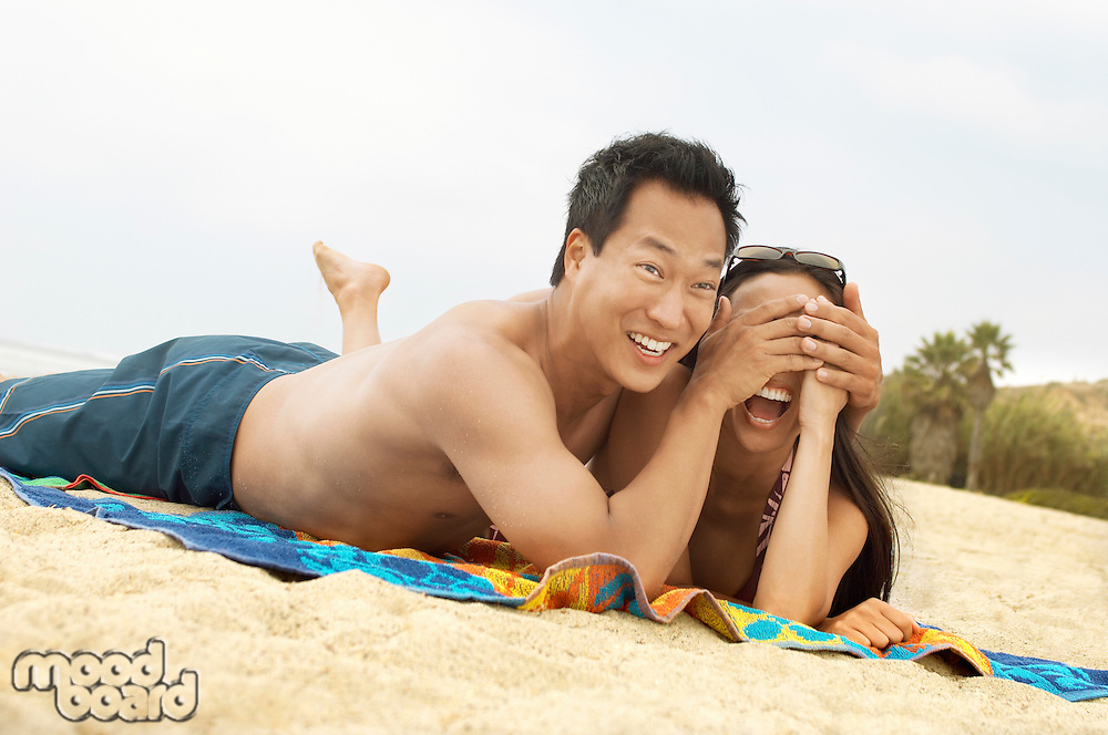 Man on Beach Covering His Girlfriend's Eyes with His Hands