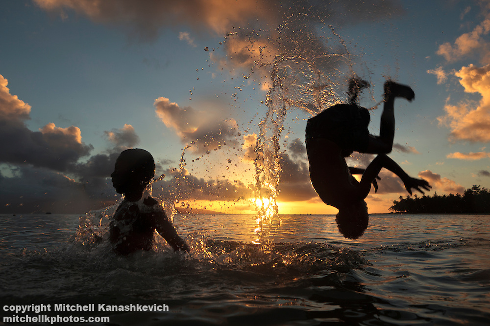 Child doing a backflip off another child's back at sunset. Rah Lava Island, Torba Province, Vanuatu