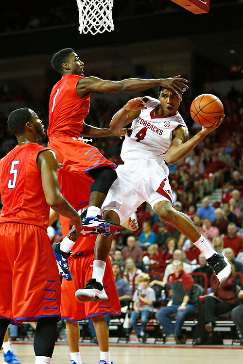 FAYETTEVILLE, AR - NOVEMBER 18:  Coty Clarke #4 of the Arkansas Razorbacks is fouled while making a pass under the basket by Ryan Manuel #1 of the SMU Mustangs at Bud Walton Arena on November 18, 2013 in Fayetteville, Arkansas.  (Photo by Wesley Hitt/Getty Images) *** Local Caption *** Coty Clarke; Ryan Manuel