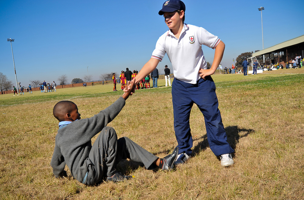 A St. Stithian College Prep student helps up an Ebony Park student during an impromptu game of rugby between kids from each school Tuesday, June 8, 2010 during a Dreamfields Project event in the Ivory Park township of Johannesburg, South Africa. The Dreamfields Project is a non-profit organization that aims to put resources for playing soccer into townships and rural areas in South Africa. Students from St. Stithians raised money to buy complete soccer uniforms for Ebony Park and another township team. Photo by Bahram Mark Sobhani