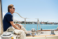 Full-length side view of man sitting on yacht