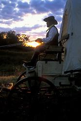 Man sitting on a western wagon at sunset