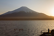 A fisherman, in silhouette, lays out nets at sunset  on Lake Yamanaka with Mount Fuji in the background Yamanashi, Japan. Thursday March 26th 2020