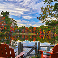 Found this idyllic and scenic New England fall foliage spot at the Kingsbury Pond in Medfield, Massachusetts. The New England fall foliage beautifully complimented the red lawn chairs. <br />