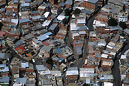 Toma aérea de una de las barriadas caraqueñas. La distribución de sus calles, y la cercanía de sus casas deja entrever una situación de sobre población. Caracas, 19 - 09 - 2005 (Ramón Lepage / Orinoquiaphoto)  )   Aerial view the city of Caracas. The city with its Modern arquitecture, Highways and contrast between the rich and poor neighborhoods is surrounded by the Avila National Park and many hills around the valley where the shanty Towns or ´´barrios¨ have grown to become one the largest in Latin America.  (Ramón Lepage / Orinoquiaphoto)