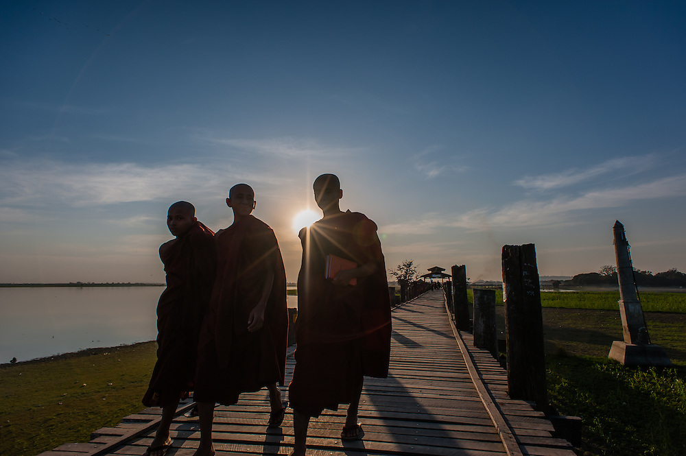 Buddhist monks strolling on U Bein bridge at dusk (Amarapura, Myanmar)