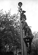 Band The Fits climbing on a lamppost, London, UK, 1980s.