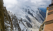 "Dôme du Goûter (center 14,121 feet or 4304 meters) is a shoulder of massive Mont Blanc (15,782 feet elevation) covered with massive glaciers such as Glacier des Bossons, seen from Aiguille du Midi, Chamonix, France, Europe..  Panorama stitched from 2 overlapping images. One of 17 photos published in Ryder-Walker Alpine Adventures ""Inn to Inn Alpine Hiking Adventures"" Catalog 2006."