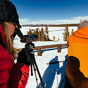Clients view wildlife through spotting scopes along the Hayden Valley in winter in Yellowstone National Park.