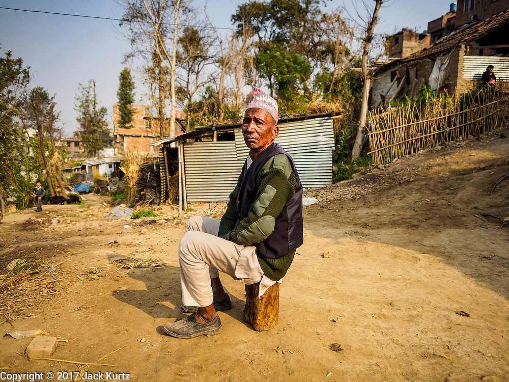 01 MARCH 2017 - KHOKANA, NEPAL: A man sits on a stool in the middle of a road in front of his temporary shelter. His home was destroyed in the 2015 earthquake. Recovery seems to have barely begun nearly two years after the earthquake of 25 April 2015 that devastated Nepal. In some villages in the Kathmandu valley workers are working by hand to remove ruble and dig out destroyed buildings. About 9,000 people were killed and another 22,000 injured by the earthquake. The epicenter of the earthquake was east of the Gorka district.     PHOTO BY JACK KURTZ