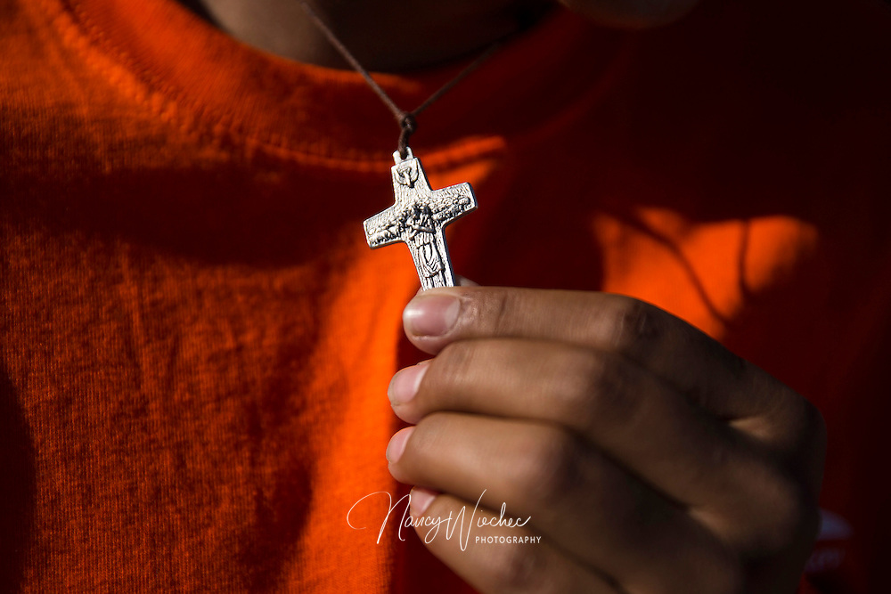 A young man holds a crucifix as he and other undocumented immigrants attend Mass with Pope Francis on the U.S. side of the border in El Paso, Texas, Feb. 17. The pope celebrated the final Mass of his Mexico visit in Ciudad Juarez. About 550 guests situated a levee north of the Rio Grande took part in the Mass. (CNS photo/Nancy Wiechec)