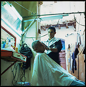 Mature Latino man getting a haircut at an old classic Cuban barber shop, old Havana, Cuba