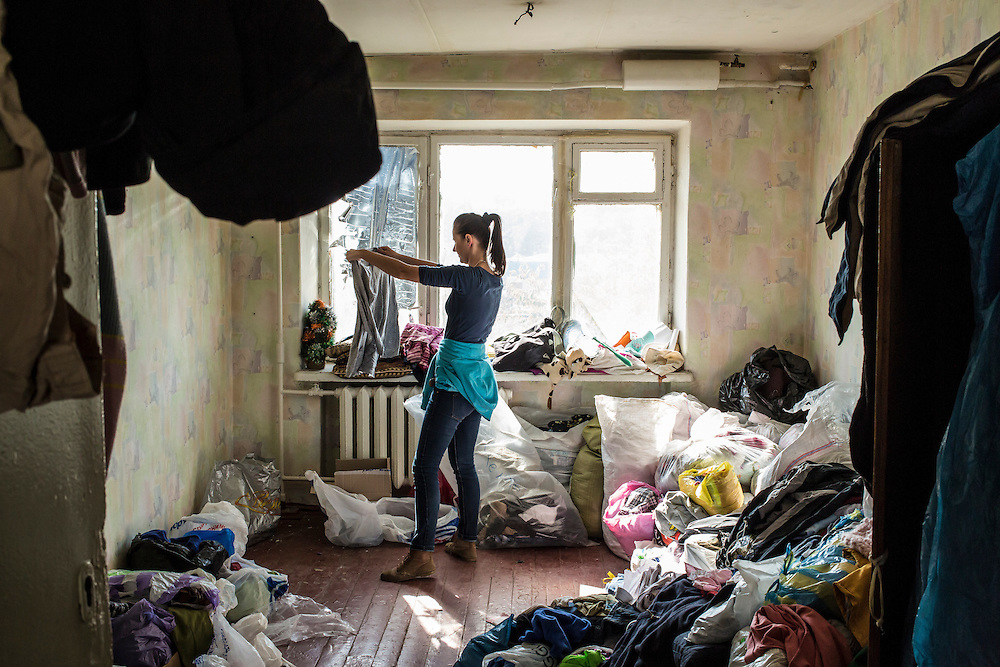 DNIPROPETROVSK, UKRAINE - OCTOBER 10: Maria Kuzminskaya, a local volunteer, sorts and folds donated clothes at The Aid of Dnipro, a charity organization providing assistance to displaced people from Eastern Ukraine, on October 10, 2014 in Dnipropetrovsk, Ukraine. While the charity has received many donations of clothes and toys, they are having a difficult time providing enough food to those in need. The United Nations has registered more than 360,000 people who have been forced to leave their homes due to fighting in the East, though the true number is believed to be much higher.(Photo by Brendan Hoffman/Getty Images) *** Local Caption *** Maria Kuzminskaya