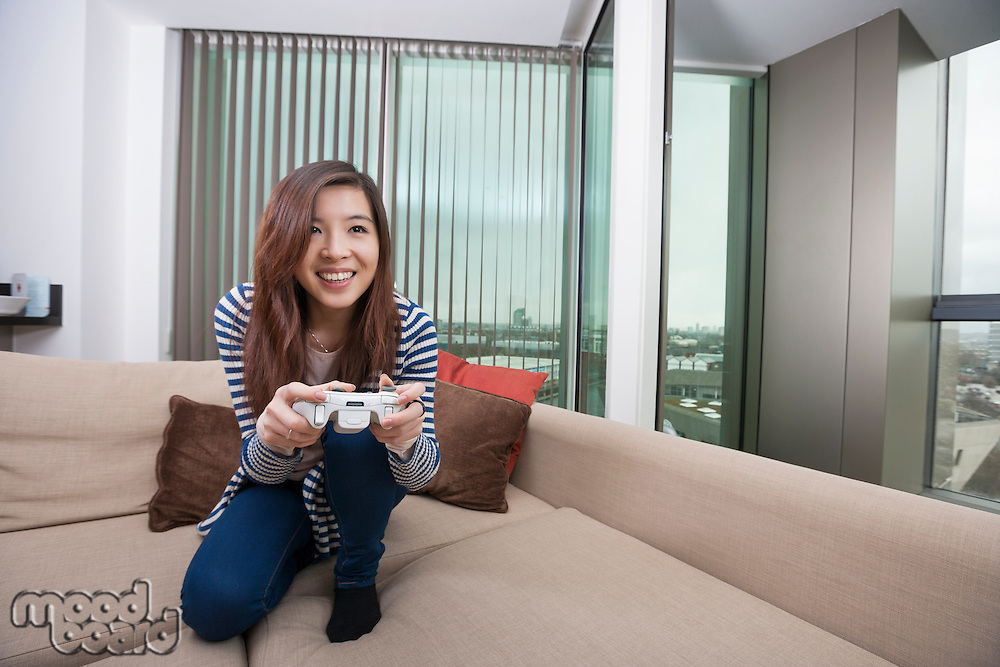 Full length of happy young woman playing video game on sofa at home