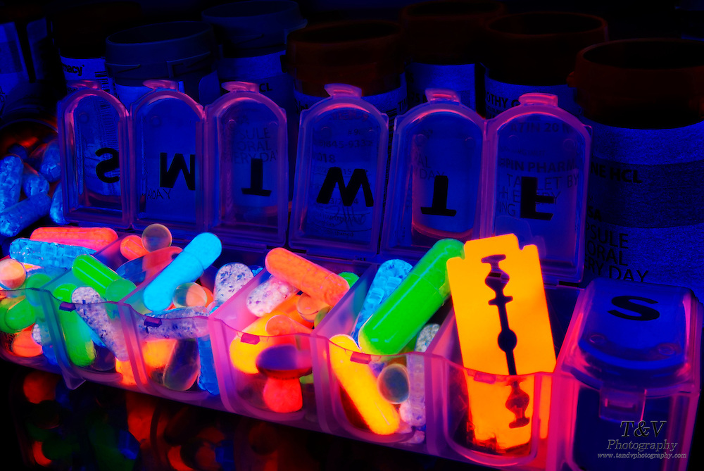 A pill organizer filled with various pills for each day of the week, including a razor blade for Friday and a closed container for the last day of the week.Black light