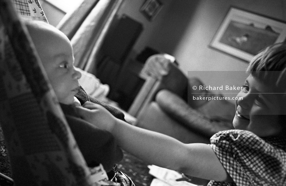 "A two and half year-old girl shows affection to her baby brother in the living room of her South London home. Reaching out to show her love, the big sister tickles the boy under his chin although he looks more intrigued than amused at the attention that this person is showing him. He is a few weeks old and lies in a baby bouncer chair on the floor. from a personal documentary project entitled ""Next of Kin"" about the photographer's two children's early years spent in parallel universes. Model released."