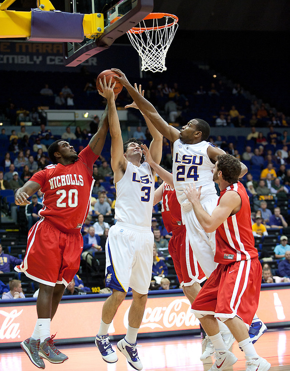 LSU Tigers forward Garrett Green (3) has his shot block by Nicholls State Colonels guard Fred Hunter (20) during the first half. LSU leads Nicholls State 25 to 21 at half time.