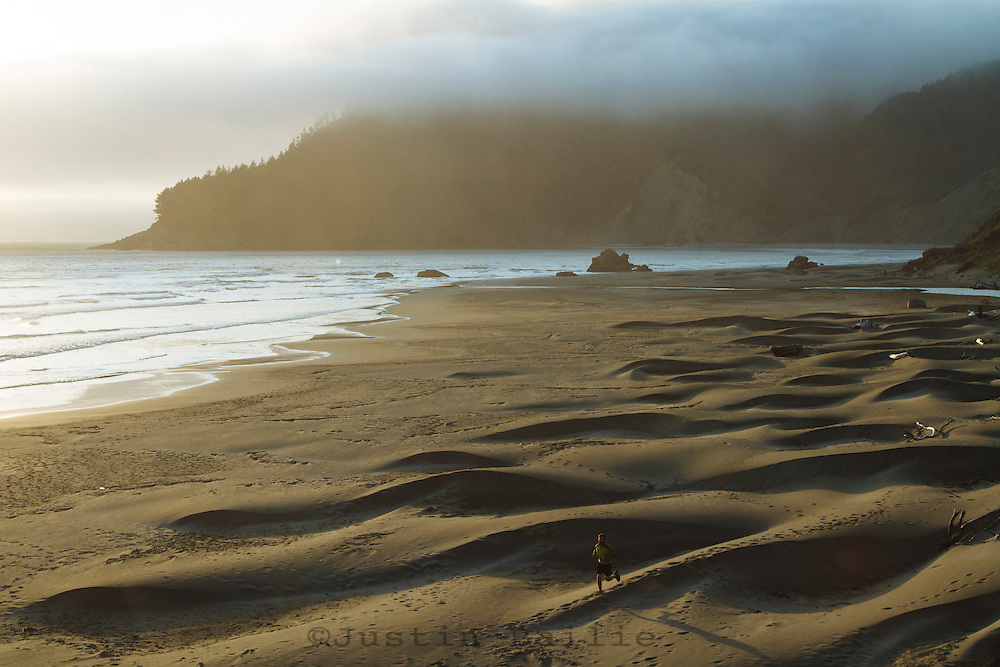 Image of man running on the beach in Southern Oregon.