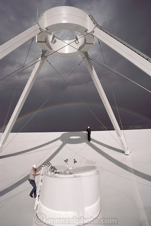 Engineers on a radio antenna under construction with rainbow on the distance. The Very Long Baseline Array (VLBA) is a system of 10 radio telescopes controlled remotely from the Array Operations Center in Socorro, New Mexico. The antennas are spread across the United States from St. Croix in the Virgin Islands to Mauna Kea on the island of Hawaii, making it the world's largest dedicated, full-time astronomical instrument..This antenna at Pie Town, New Mexico, is now linked with the Very Large Array via fiber optics. It is the first part of the planned Expanded Very Large Array...(1988)