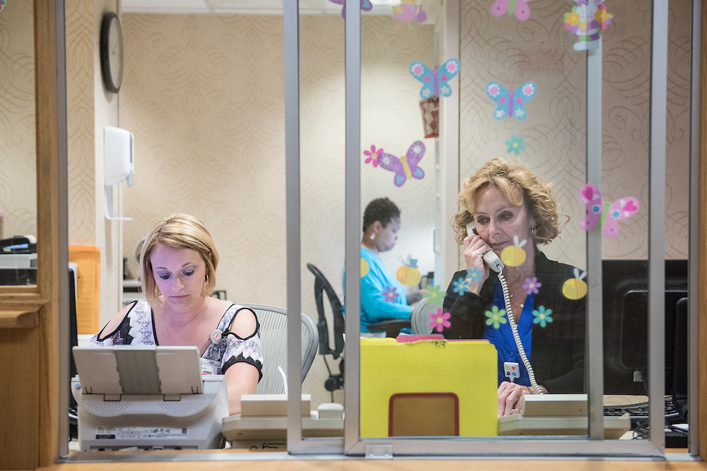 Seated in the registration window are Elizabeth Torez, left, with Lois Bickett and Robbin Washington, photographed Thursday, May 21, 2015 at Baptist Health in Lexington, Ky. (Photo by Brian Bohannon/Videobred for Baptist Health)
