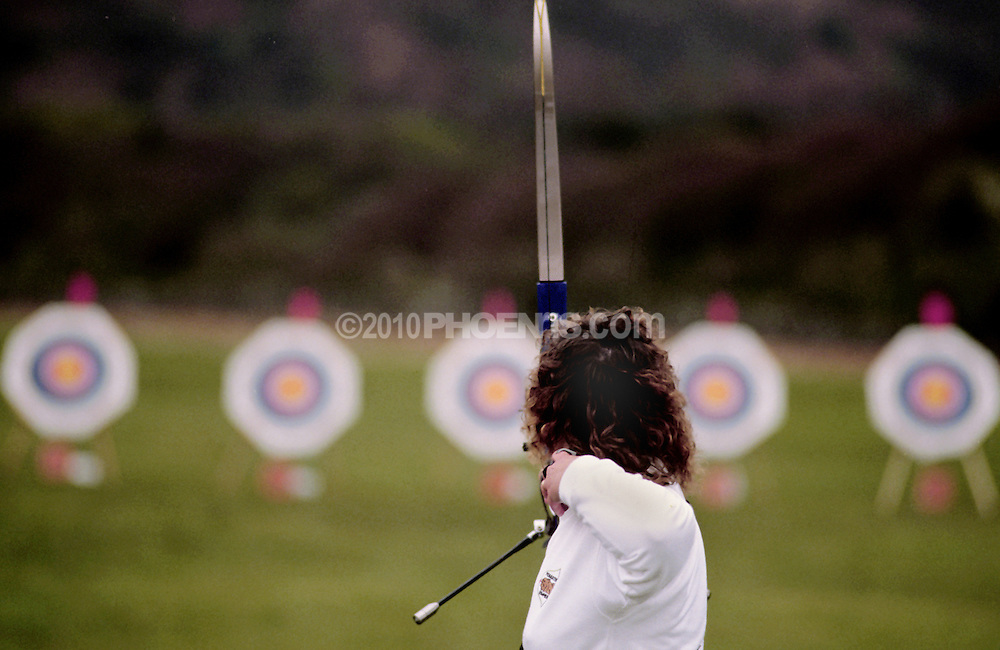 Archery competitor aims bow and arrow at targets. SPORT