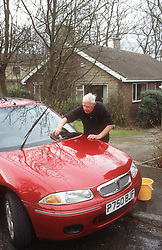 Man washing car on Sunday morning,