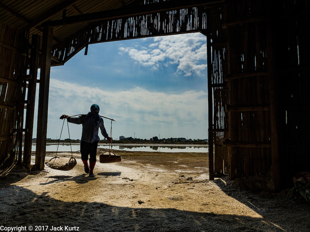 22 FEBRUARY 2017 - BAN LAEM, PETCHABURI, THAILAND: A salt field worker carries salt into a warehouse during the salt harvest in Petchaburi province of Thailand, about two hours south of Bangkok on the Gulf of Siam. Salt is collected in coastal flats that are flooded with sea water. The water evaporates and leaves the salt in large pans. Coastal provinces south of Bangkok used to be dotted with salt farms, but industrial development has pushed the salt farms down to remote parts of Petchaburi province. The harvest normally starts in early February and lasts until early May, but this year's harvest was delayed by a couple of weeks because of unseasonable rain in January that flooded many of the salt collection ponds.    PHOTO BY JACK KURTZ
