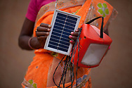 Jiyamuni Murmu, 35, in orange sari, a SAMVAD beneficiary shows her D-light solar panel lamp in Rupabad Jharkhand, India Tuesday, Oct. 9, 2012 (Photo/Elizabeth Dalziel for Christian Aid)