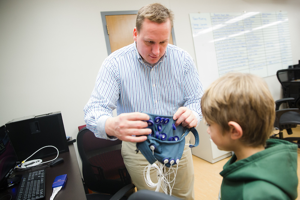Dr. Richard Lamb, associate professor of science education measurement at Washington State University, assists a student from Sunnyside Elementary with an EEG aparatus used to mearure brain activity.