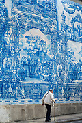 Man with walking cane passes azulejos Portuguese blue and white wall tiles of Capela das Almas de Santa Catarina  - St Catherine's Chapel in Porto, Portugal