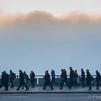 London, UK - 13 March 2014: commuters cross London Bridge as London wakes up under heavy fog