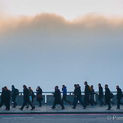 London, UK - 13 March 2014: commuters cross London Bridge as London wakes up under heavy fog
