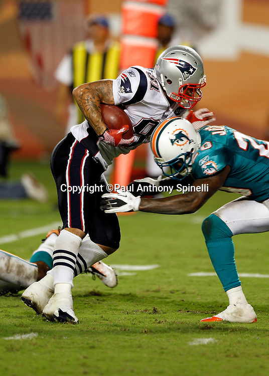 New England Patriots tight end Aaron Hernandez (81) catches a pass and gets tackled by Miami Dolphins defensive back Reshad Jones (20) during the NFL week 1 football game against the Miami Dolphins on Monday, September 12, 2011 in Miami Gardens, Florida. The Patriots won the game 38-24. ©Paul Anthony Spinelli