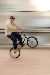 "Asia, Japan, Tokyo.  Teenager doing ""wheelie"" on bicycle (blurred motion)."