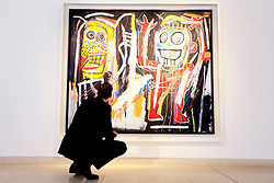 © Licensed to London News Pictures 10/04/2013.A Christie's employee admires Jean-Michel Basquiat's painting 'Dustheads' (estimated between $25-35 million) that, along with other major Abstract Expressionist works, are on display at Christie's in central London, and due to go on auction on 15th May in New York. .London, UK.Photo credit: Anna Branthwaite