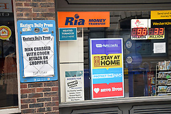 Eastern Daily Press headline next to NHS digital poster in newsagent window during Coronavirus lockdown, Norwich UK April 2020