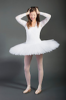 Young female ballet dancer screaming over grey background