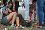 Anderson Allen, left, holds her niece Finesse Dillard near 500 Genesee Street in Rochester on Thursday, August 20, 2015. Three were fatally shot and another four injured in a drive-by shooting in front of the Boys and Girls Club of Rochester the night before.