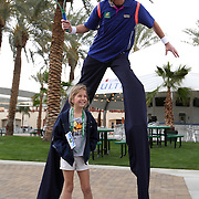 March 1, 2014, Palm Springs, California: <br /> A man on stilts poses with a fan during Kids Day at the Indian Wells Tennis Garden sponsored by the Coachella Valley National Junior Tennis and Learning Network.<br /> (Photo by Billie Weiss/BNP Paribas Open)