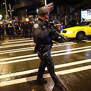 A Seattle Police officer keeps protesters back in front of the Sheraton Hotel during an Occupy Seattle protest where Chase Bank CEO Jamie Dimon was speaking on Wednesday, November 2, 2011. A few hundred people tried to block the doors to the hotel during an event hosted by the University of Washington business school. (Joshua Trujillo, seattlepi.com)