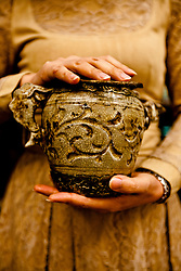 The owner of the Hoa Lu Fine Arts and Handicrafts Company in Hanoi, Vietnam, holds a replica of an old teapot.