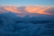 The golden light of sunset lights up high level cirrostratus clouds, high above a bank of lower-level cumulonimbus clouds that are already in the shade in this aerial view taken over King County, Washington.